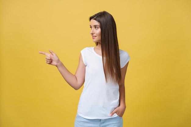 노란색 배경에 입을 벌리고 있는 동안 손가락으로 한쪽을 가리키는 젊은 여성을 놀라게 합니다.
