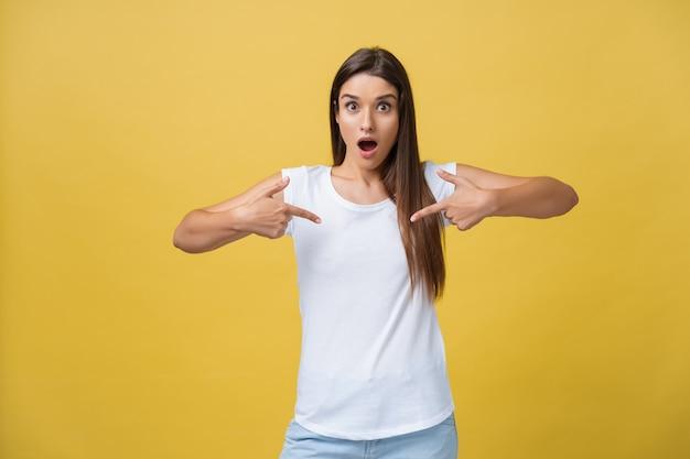 Удивите молодую женщину, указывая пальцем в одну сторону, открывая рот на желтом фоне