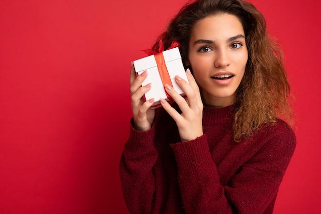 카메라를 찾고 흰색 선물 상자를 들고 어두운 빨간색 스웨터를 입고 빨간색 배경 벽 위에 절연 놀된 성인 갈색 머리 곱슬 여자. 복사 공간, 모형