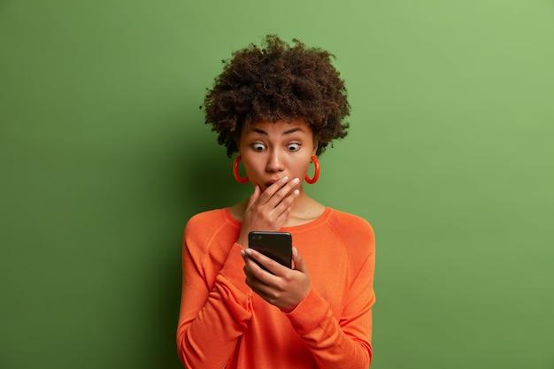 驚いた大人の女性は、深く驚いて、スマートフォンのディスプレイを見つめ、ウェブサイトで衝撃的なニュースを読み、オレンジ色のジャンパーを着て、目をつぶって、口を覆っています。ああ、その恐ろしい!