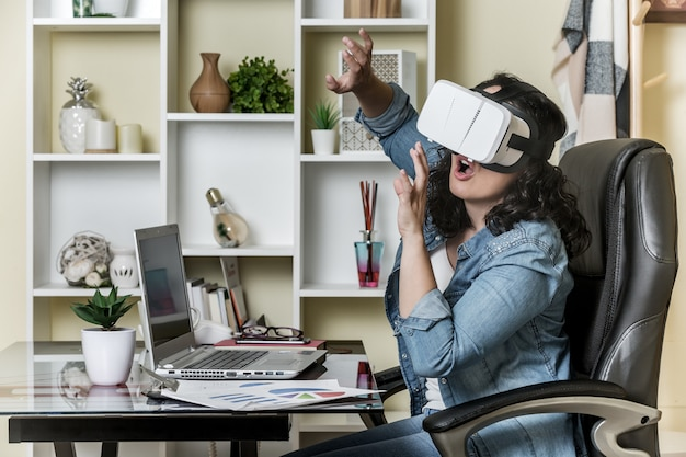 Изумленная взрослая женщина в шлемофоне виртуальной реальности пока сидящ на столе с компьтер-книжкой в современном офисе