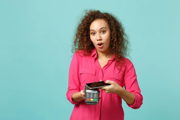 驚いたアフリカの女の子は、青いターコイズブルーの背景に分離されたクレジットカード決済の取得を処理するために携帯電話のワイヤレス現代銀行決済端末を保持しています。人々のライフスタイルの概念。コピースペースをモックアップします。