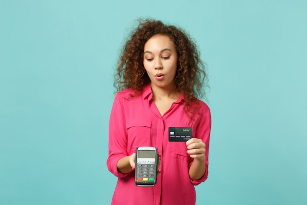 Amazed african girl hold wireless modern bank payment terminal to process, acquire credit card payments isolated on blue turquoise background. people emotions, lifestyle concept. mock up copy space.