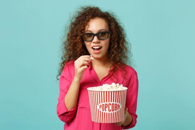 3d 아이맥스 안경을 쓴 아프리카 소녀가 영화 영화를 보고 스튜디오의 파란색 청록색 벽 배경에 격리된 팝콘을 들고 놀랐습니다. 영화, 라이프 스타일 개념에서 사람들의 감정. 복사 공간을 비웃습니다.
