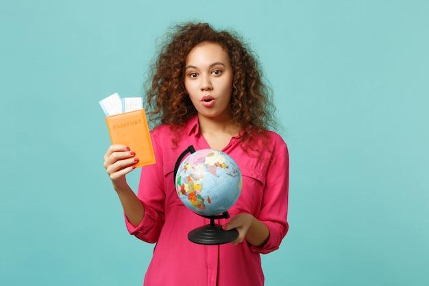 地球の世界の地球儀、パスポート搭乗券、青いターコイズブルーの背景で隔離のカジュアルな服を着て驚いたアフリカの女の子。人々の誠実な感情、ライフスタイルのコンセプト。コピースペースをモックアップします。
