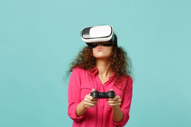 Пораженная африканская девушка в повседневной одежде смотрит в гарнитуру и играет в видеоигру с джойстиком, изолированным на синем бирюзовом стенном фоне. люди искренние эмоции, концепция образа жизни. копируйте пространство для копирования.