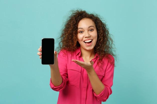 青いターコイズブルーの壁の背景に分離された空白の空の画面で携帯電話に手を指しているカジュアルな服を着て驚いたアフリカの女の子。人々の誠実な感情、ライフスタイルのコンセプト。コピースペースをモックアップします。