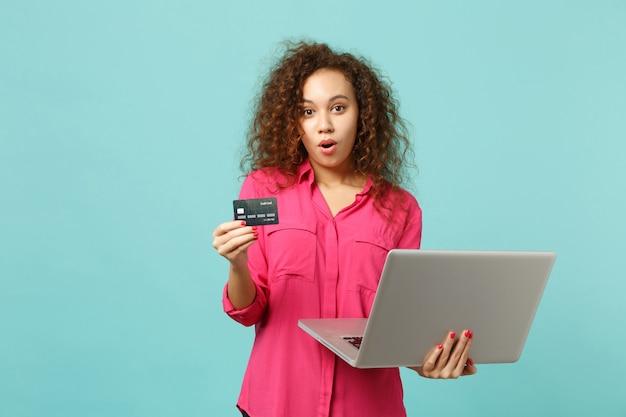 スタジオで青いターコイズブルーの背景に分離されたクレジットバンクカードを保持しているラップトップpcコンピューターを使用してカジュアルな服装で驚いたアフリカの女の子。人々の誠実な感情のライフスタイルの概念。コピースペースをモックアップします。