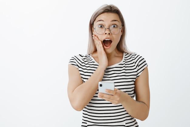 Пораженная и удивленная блондинка позирует в студии со своим телефоном