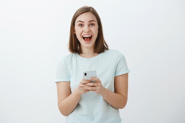 Пораженная и взволнованная привлекательная молодая европейская модель, широко улыбаясь от замечательных новостей, полученных через интернет, держит смартфон, взволнованный и восхищенный взглядом позируя на белой стене