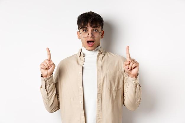 Пораженный и возбужденный мужчина в очках показывает потрясающую промо-сделку, показывает пальцами вверх и в благоговении открывает рот, стоит на белом фоне