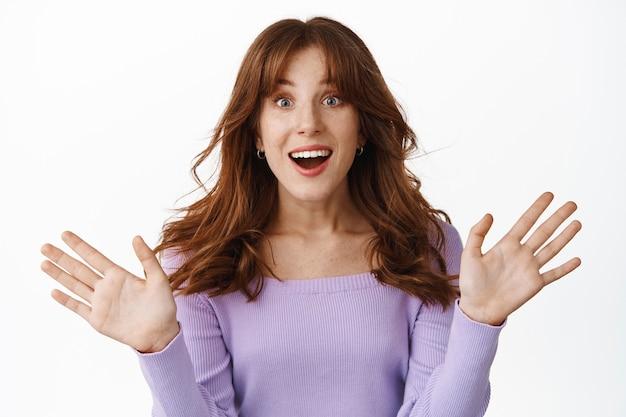 驚いて興奮した赤毛の女性は、手を横に広げ、幸せに喘ぎ、勝利し、驚くべきニュースを聞き、祝い、白の上に立っています。