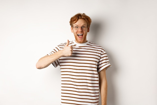 Пораженный и очарованный рыжий парень проверяет что-то классное, показывает вверх большой палец и радостно кричит да, стоя на белом фоне.