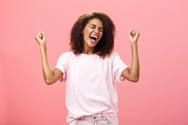 Пораженная и счастливая триумфальная афро-американская спортсменка празднует победу, кричит от удивительных волнующих чувств, закрыв глаза, поднимая кулаки в знак победы, стоя над розовой стеной