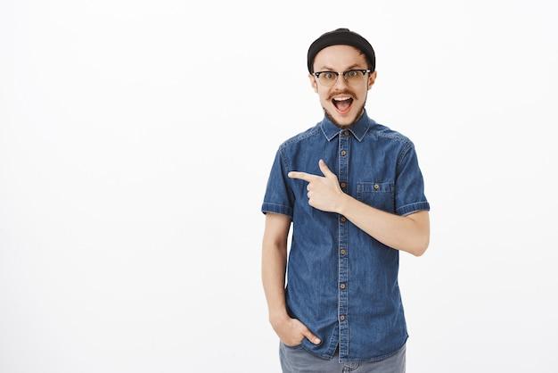 Пораженный и впечатленный красивый взрослый бородатый парень в синей рубашке и черной шапке, указывающий влево указательным пальцем и широко улыбающийся от восторга и радости, находясь в восторге