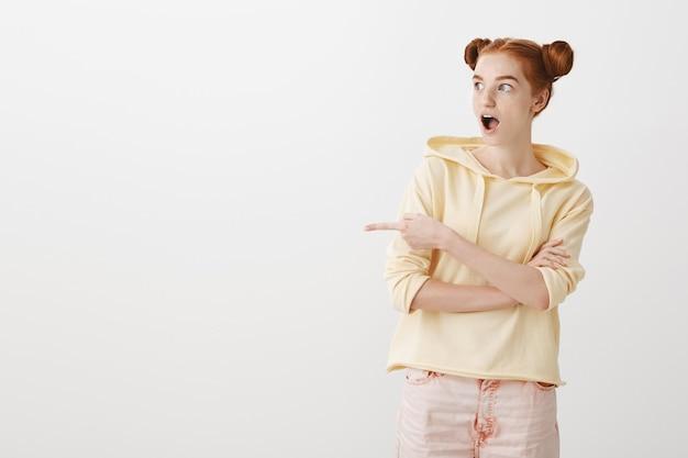 Пораженная и впечатленная рыжая девочка-подросток показывает пальцем влево