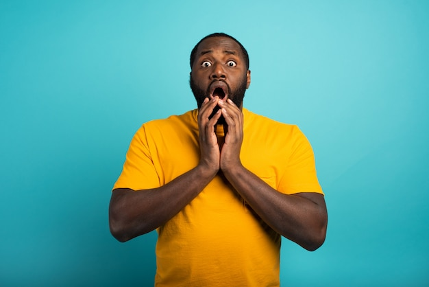 Удивленное и шокированное выражение черного мальчика над голубым