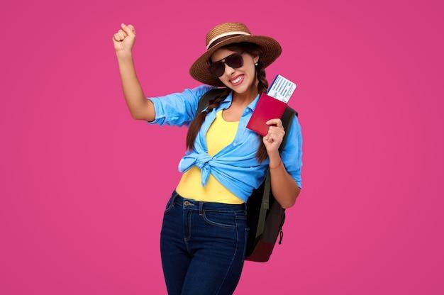 Пораженная и улыбающаяся женщина-путешественница в соломенной шляпе и солнечных очках с билетом на самолет и паспортом на розовом изолированном фоне
