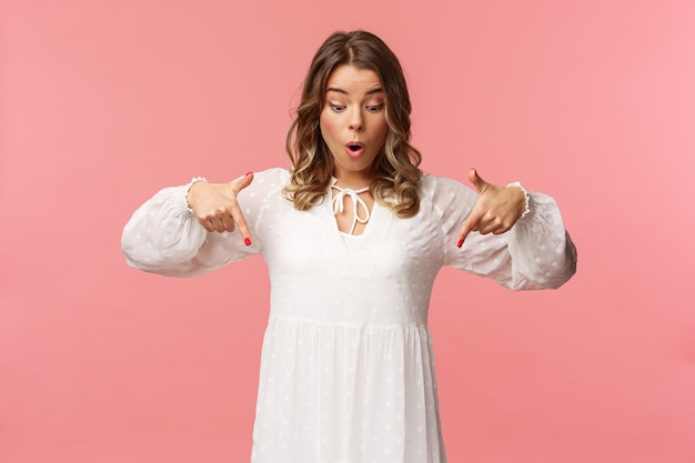 놀랍고 궁금해하는 잘 생긴 금발의 유럽 여성 20 대, 아름다운 흰색 드레스를 입고,보고 가리키며, 굉장하고 숨이 멎을듯한 핑크색 벽을보고 놀랐습니다.