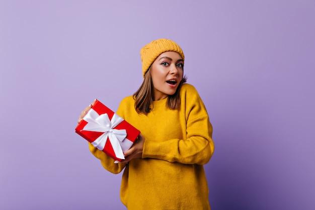 Пораженная привлекательная девушка в желтом наряде позирует с подарком на день рождения. добродушная женщина в элегантном свитере веселится на рождество.