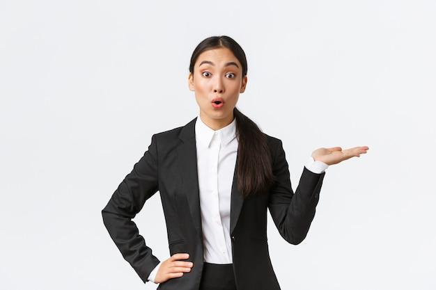 Пораженная азиатская бизнес-леди в черном костюме показывает рукой вправо и заинтересованно смотрит в камеру, обсуждает объявление, показывает баннер, стоит на белом фоне заинтригована. копировать пространство