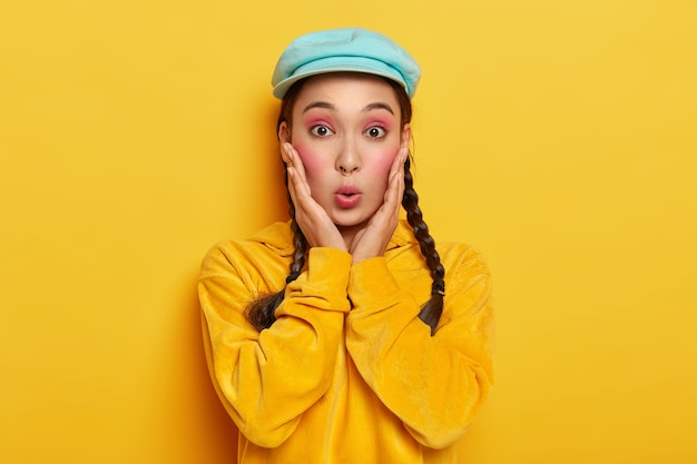 驚いたアジアの女性は唇を丸く保ち、驚きで見え、ゴシップに反応し、スタイリッシュな帽子とコーデュロイの黄色いスウェットシャツを着ています