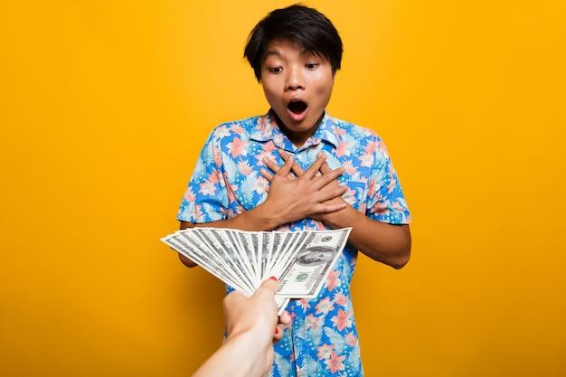 Amazed asian man receiving money banknotes