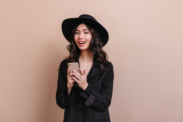 Amazed asian woman holding smartphone and looking at camera. elegant curly woman in coat posing with gadget.