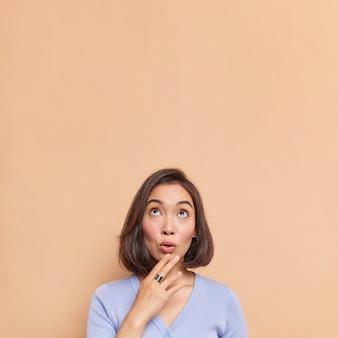 上に焦点を当てた黒髪の驚いたアジアの女性は、衝撃的な何かに反応しますあごに手を保ちますあなたの昇進のためにベージュの壁の空白のコピースペースのオーバーヘッドに対して青いジャンパーポーズを着ています