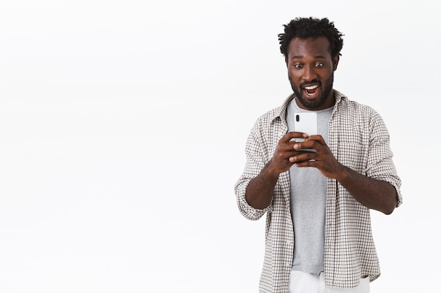 Amazed and astonished african-american bearded guy recording some awesome video