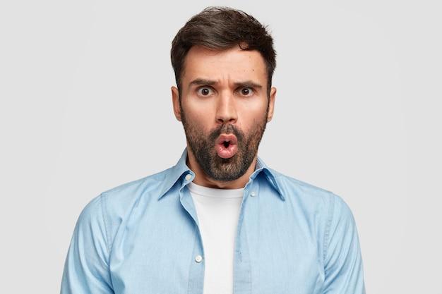 Изумленный изумленный бородатый парень недовольно смотрит, сердито хмурится