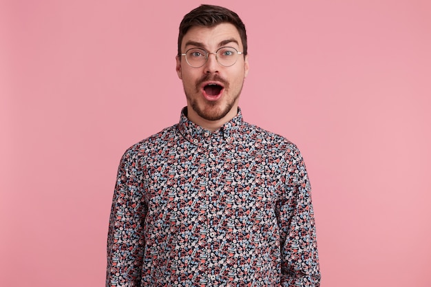 Amazed attractive handsome young man wearing glasses with dark hair unshaved with beard and mustache in colorful shirt opened mouth in excitement, isolated