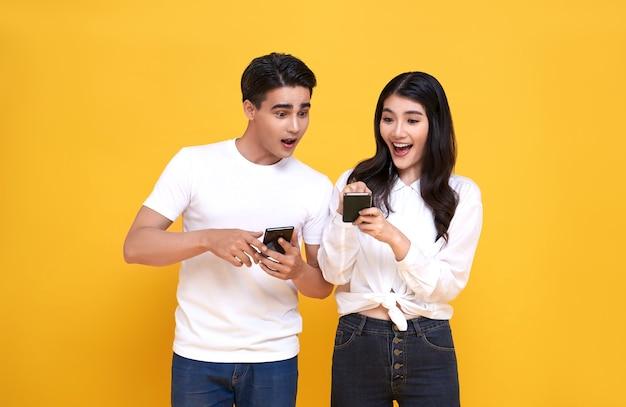 Пораженная привлекательная молодая азиатская пара, вместе глядя на смартфон, изолирована на желтом фоне.