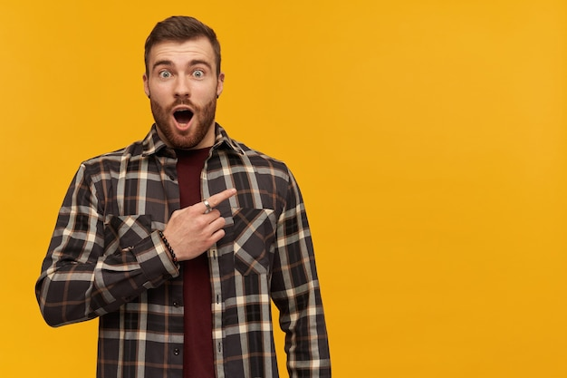 Amazed attractive young bearded man in plaid shirt with opened mouth looks astonished and pointing away to the side over yellow wall