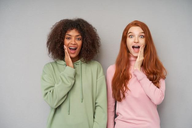 Giovani donne attraenti stupite che tengono i palmi sollevati sulle guance e guardando sorpreso con gli occhi spalancati e le bocche aperte, isolate su un muro grigio