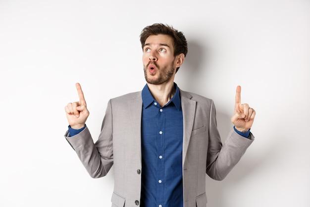 Пораженный бородатый парень в деловом костюме, указывая и глядя вверх, удивился, сказал «вау» и показал захватывающую вещь, стоя на белом фоне.