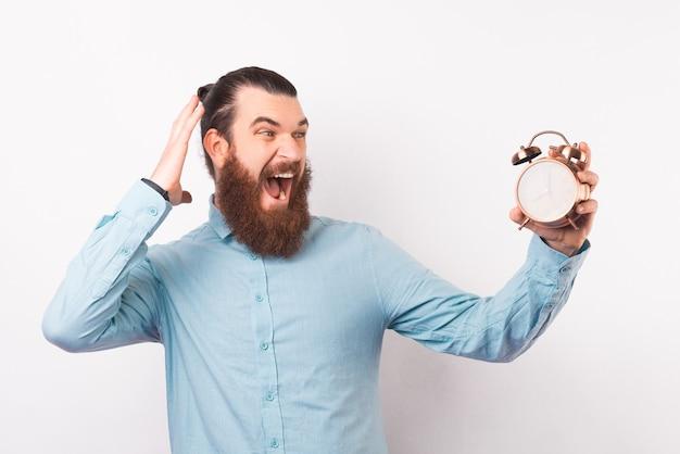驚いたあごひげを生やしたヒップスターは、彼が持っている目覚まし時計を見ています。