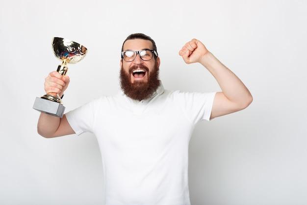 Пораженный бородатый хипстер в белой футболке празднует и держит чемпионский кубок