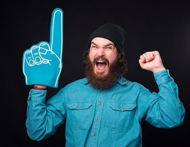 Amazed bearded hipster man pointing with fan glove and celebrating victory of favorite team