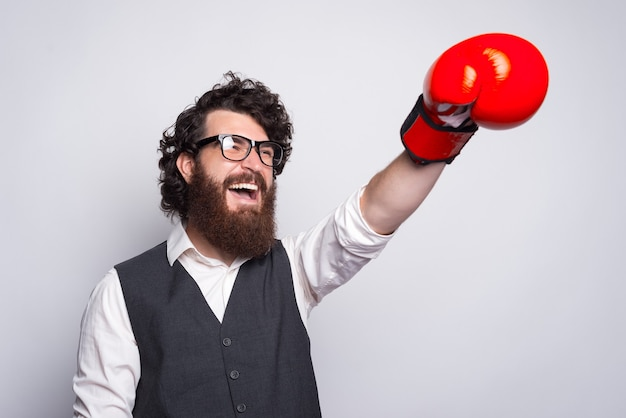 Amazed bearded hipster man in suit punching with red glove box.