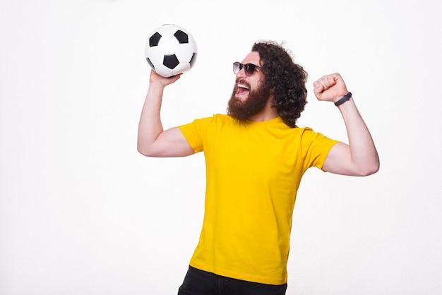 Изумленный бородатый хипстер с длинными вьющимися волосами держит футбольный мяч и празднует успех