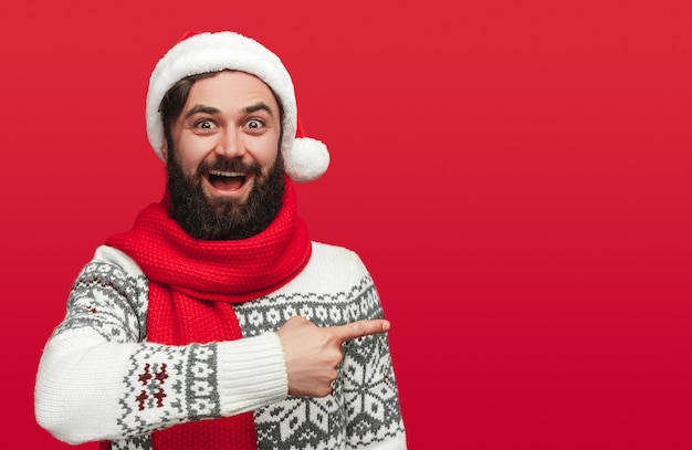 Amazed bearded male in christmas sweater and santa hat