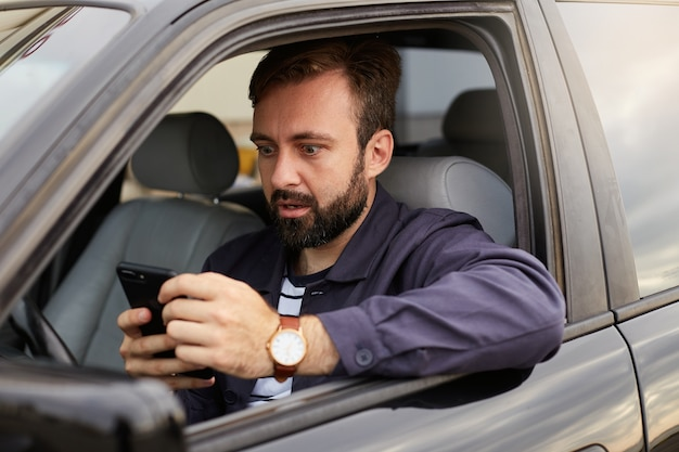 Amazed bearded man in a blue jacket and striped t-shirt, sits behind the wheel of the car, holds the phone in his hands and stares in surprise.