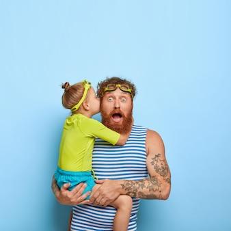 놀란 수염 난 남자는 딸의 비밀을 듣고 겁에 질린 표정으로 응시하며 고글과 줄무늬 조끼를 착용합니다. 빨간 머리 소녀는 그녀의 아빠의 귀에 뭔가를 속삭