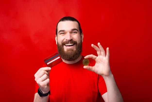 Пораженный бородатый мужчина держит кредитную карту и биткойн