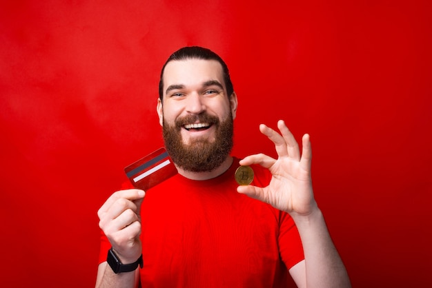 Amazed bearded man holding credit card and bitcoin