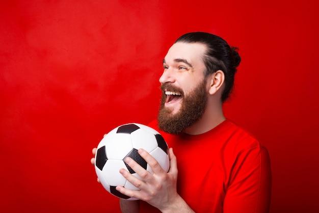 Пораженный бородатый мужчина держит футбольный мяч и поддерживает свою команду