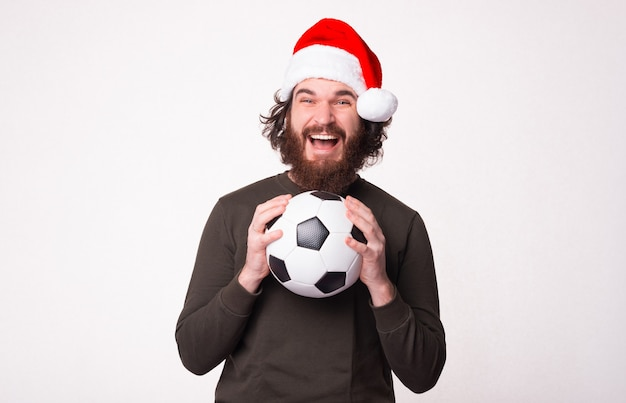 Amazed bearded man holding soccer ball and screaming and wearing santa claus hat