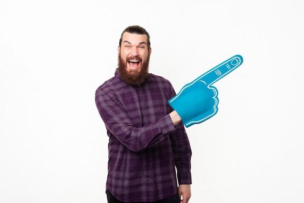Пораженный бородатый мужчина в клетчатой рубашке указывает в сторону перчаткой из пенопласта