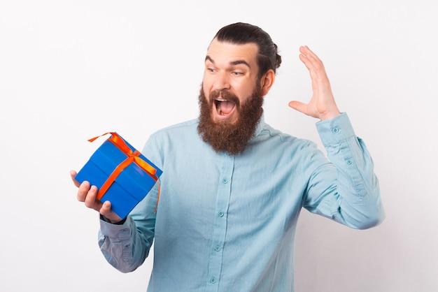 Пораженный бородатый мужчина в восторге от подарочной коробки.
